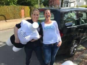 Daniela und Julia mit Musterpuppe und Kaiserschlüpfer-Shirt vor dem Auto auf dem Weg nach Kassel